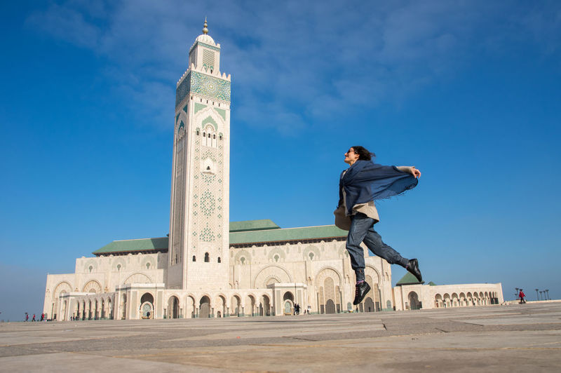 Full length of woman jumping outside hassan ii mosque