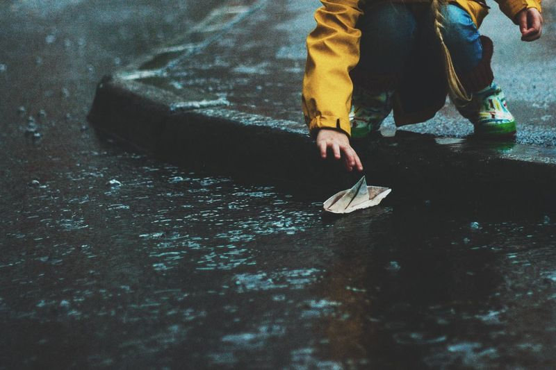 Low section of girl with paper boat on road during rain