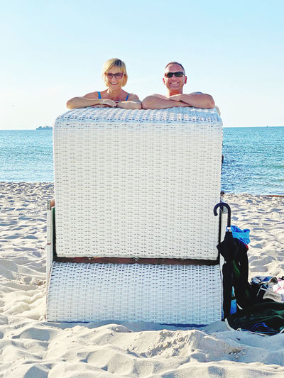 Men sitting on beach by sea against sky