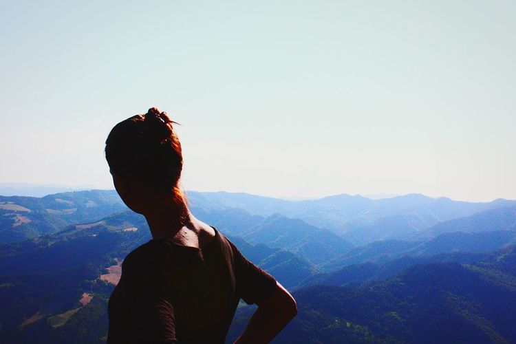 Woman looking at mountains against clear sky