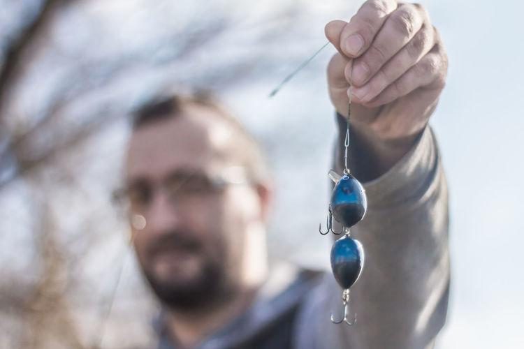 Close-Up Of Man Holding Blue Fishing Bait
