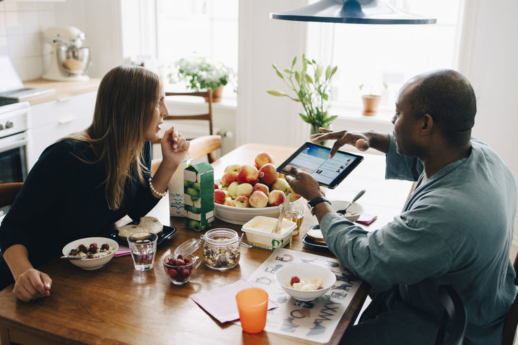 Man and woman using phone while sitting on table
