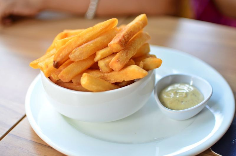 French fries in bowl with ketchup on table