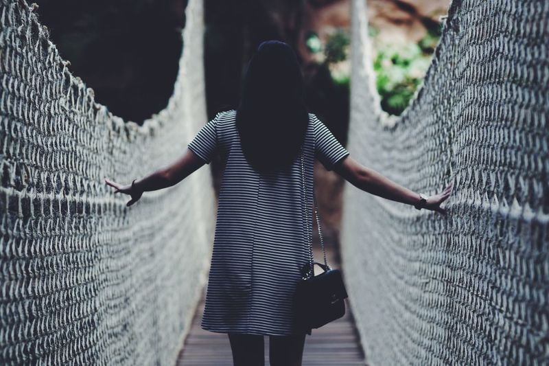 Rear view of young woman standing on footbridge