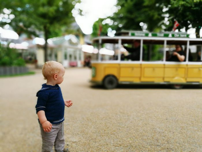 Boy looking away while standing outdoors
