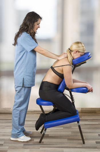 Chiropractor, physiotherapist examining her patient back and doing decontracting massage. Osteopathy. Back Doctor  Exercising Medicine Pain Woman Chair Massage Chiropractor Clinic Female Hand Health Healthcare And Medicine Massage Massage Therapy Muscle Osteopathy Patient Physiotherapy Professional Stretching Terapy Treatment