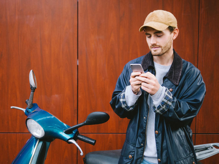 Portrait of young man using mobile phone by scooter
