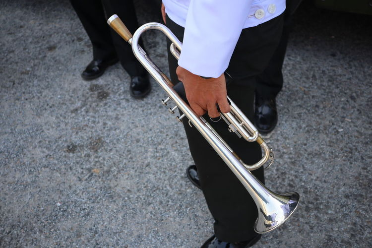 Midsection of man holding trumpet while standing on road