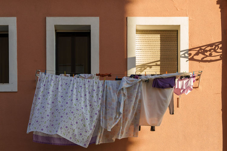 Laundry drying by windows outside house