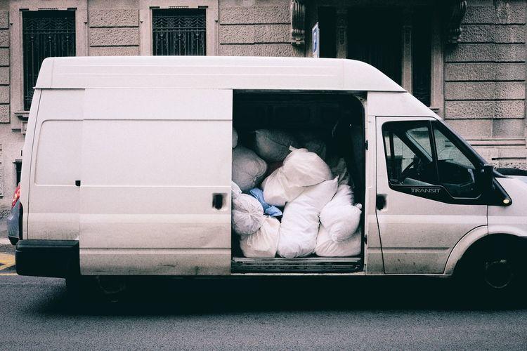 Sacks in van on street against building
