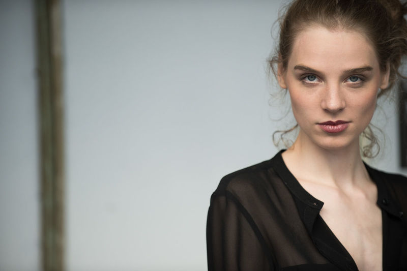 Portrait of beautiful young woman against wall