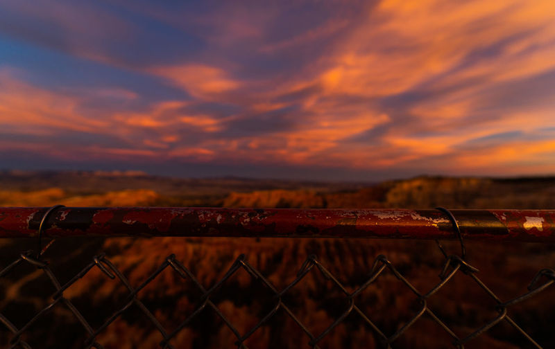 Sky Fence Cloud - Sky Metal Protection Security Sunset Boundary Barrier Chainlink Fence Nature No People Safety Scenics - Nature Focus On Foreground Outdoors Field Land Beauty In Nature Dramatic Sky
