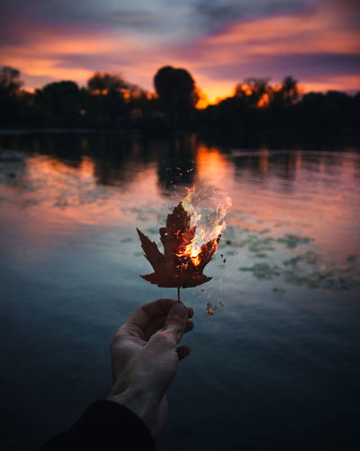 Cropped Hand Holding Burning Autumn Leaf Against Lake During Sunset