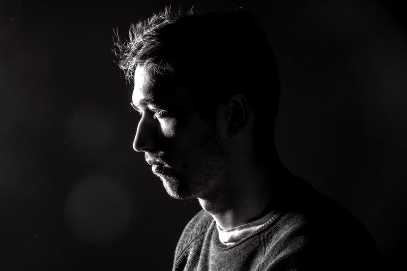 Profile view of man with stubble over black background