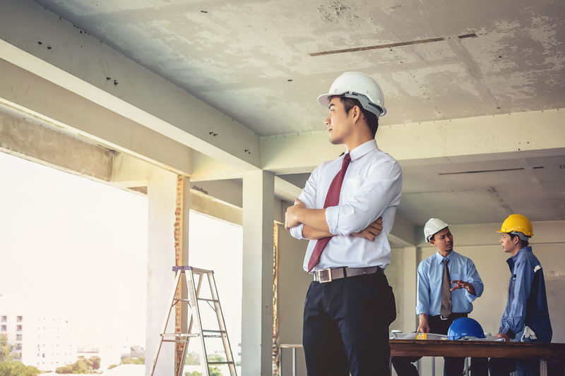 Confident Engineer With Colleagues Standing At Construction Site