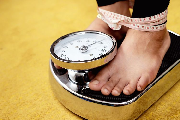 Close-up of woman standing on weighing scale