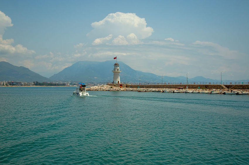 Alanya Lighthouse Alanya Harbor Lighthouse Mediterranean  Mediterranean Sea Turkey Architecture Bay Beauty In Nature Blue Building Building Exterior Built Structure Clouds And Sky Mountain Mountain Range Nature Scenics - Nature Sea Sky Tranquil Scene Travel Turkish Flag Water Waterfront