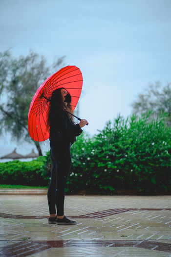 Full length of woman standing on wet road during rainy season
