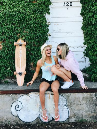 Two young girlfriends sitting on a step during summer laughing and talking to each other with a longboard and green leaves in the background. Sitting Two People Togetherness Outdoors Casual Clothing Smiling Day Happiness Blond Hair Leisure Activity Friendship Summer Full Length Bonding Young Women Young Adult Adult Cheerful Portrait People Longboarding Longboard Girl Friendship ❤ Friendship Goals Womensfashion