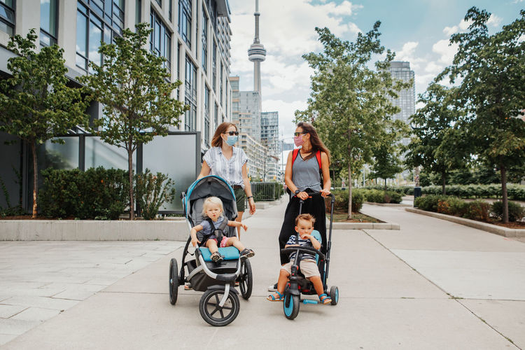 Two moms with strollers and kids walking together. women in face masks with children outdoor