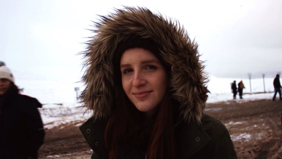 Portrait Of Young Woman Wearing Warm Clothes While Standing On Snow Covered Field
