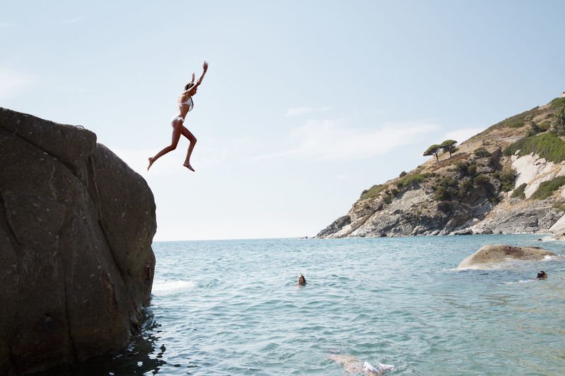 People jumping on rock by sea against sky