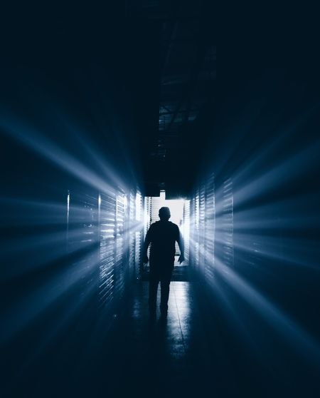 Rear View Of Silhouette Man Walking Amidst Light Streaming In Corridor