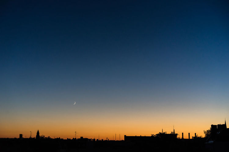 Silhouette city against clear sky during sunset