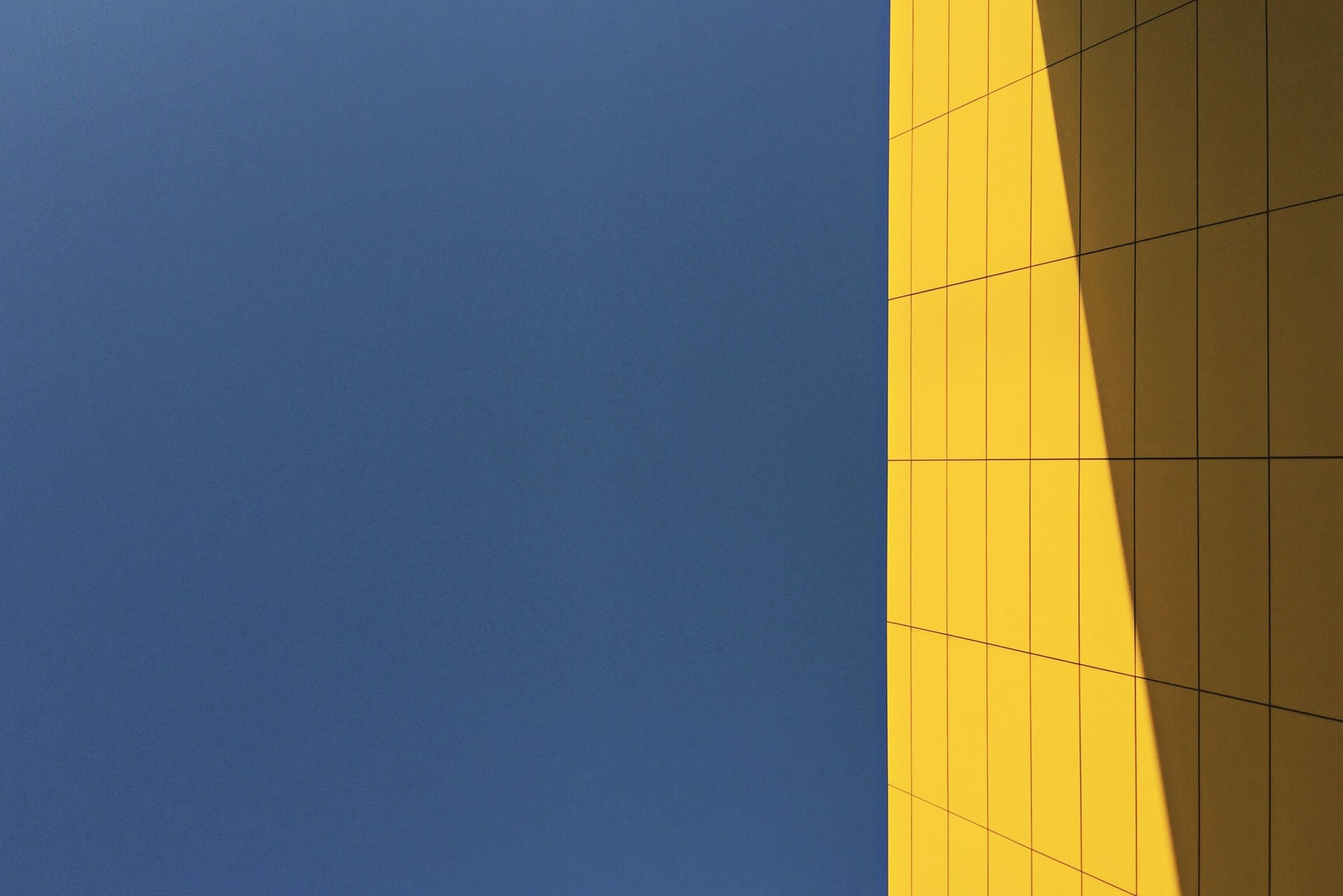 yellow, copy space, blue, clear sky, built structure, wall - building feature, architecture, no people, outdoors, low angle view, day, wall, guidance, part of, multi colored, communication, cropped, building exterior, backgrounds, pattern