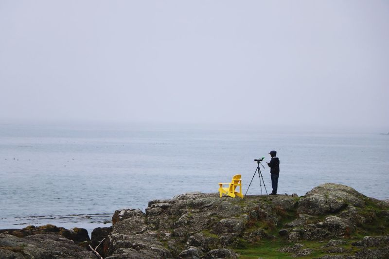 Man Photographing While Standing On Rock By Sea Against Sky