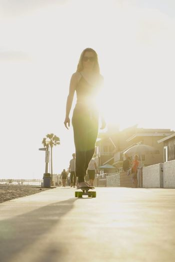 Athleisure Slow roll on the Skateboard down the boardwalk California Sunshine