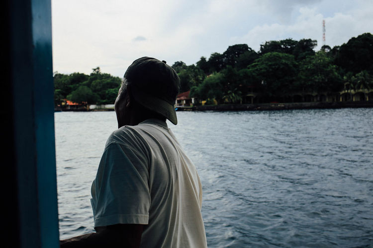 Man Looking At View While Sailing On Boat In River Against Sky