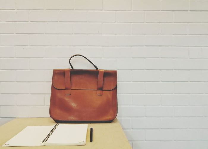 Bag and spiral notebook by pen on table against brick wall