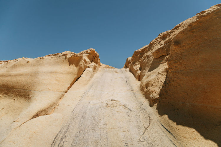 Low Angle View Of Road Amidst Rock Formations Against Clear Blue Sky