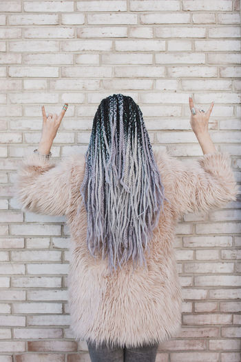Rear View Of Woman Wearing Fur Coat While Gesturing Horn Sign Against Brick Wall