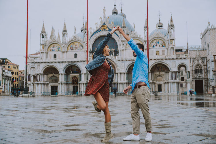 Young couple dancing against historic building