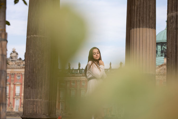 Close-up of young woman standing against columns