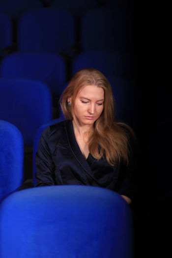Sad young woman sitting on blue chair in darkroom
