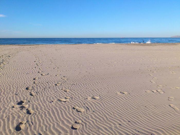 Footprints on sand at beach against clear blue sky