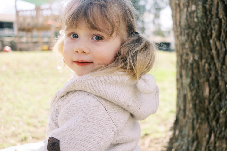 Portrait of cute girl against tree trunk