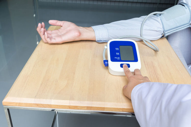 Cropped hand of doctor checking blood pressure of male patient at table