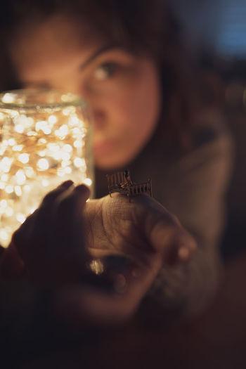 Portrait of woman holding illuminated lighting equipment in jar
