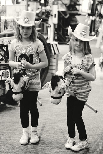 Young Girls With Toy Horses And Cow Girl Hats WALKING IN CITY