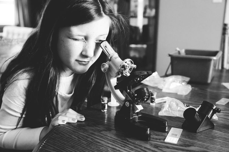 Girl Using Microscope At Table In School