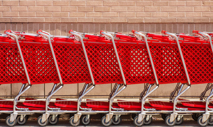 Row of red shopping carts by brick wall Architecture Brick Wall Building Exterior Built Structure Close-up Consumerism Day Group Of Objects Hanging In A Row Large Group Of Objects Metal No People Order Outdoors Red Repetition Shopping Shopping Cart Side By Side Wall - Building Feature