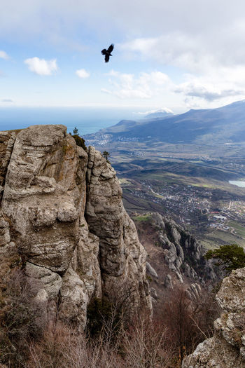 Sky Mountain Scenics - Nature Beauty In Nature Cloud - Sky Rock Solid Bird Tranquility Rock - Object Landscape Vertebrate Animal Themes Nature Tranquil Scene Mountain Range Flying Day Rock Formation Animal Outdoors Formation