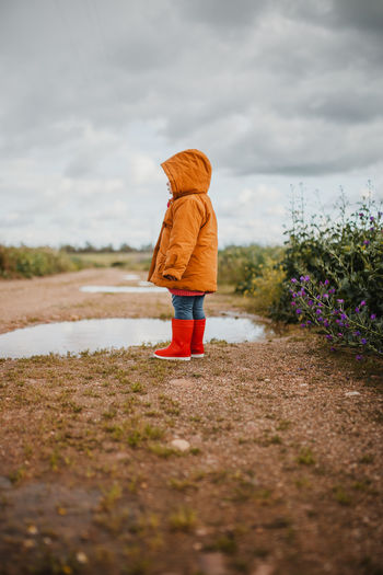 Rear view of boy standing on land against sky