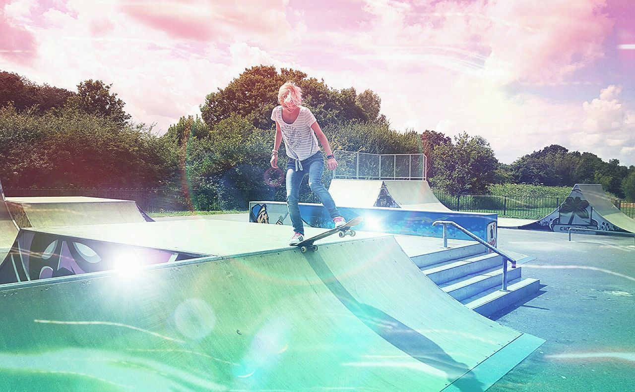 Young woman skateboarder on ramp in skateboard park