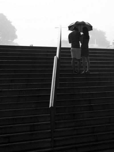 Couple with same black white striped motifs Architecture Blackandwhite Photography Building Exterior Built Structure Couple Couple With Umbrellas Day Full Length Leisure Activity Lifestyles Low Section Men Outdoors People Real People Rear View Singapore People Singaporestreetphotography Sky Steps Steps And Staircases Street Photo Singapore Streetphotography Walking