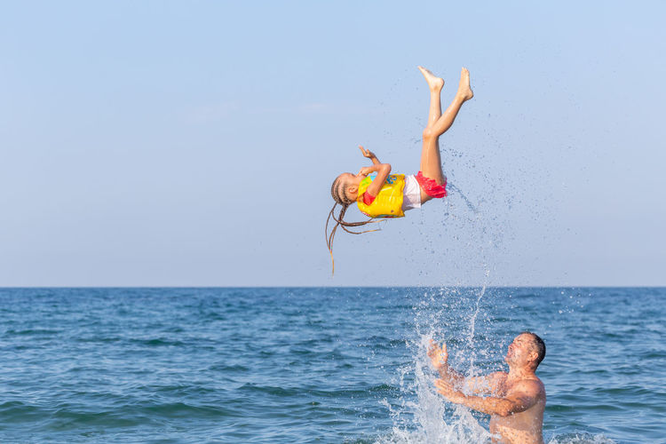 Strong man in sea tosses a 4-5 year girl. acrabatic trick against background of blue sky and sea